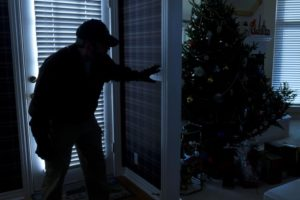 Shadowed thief breaking into a home at night through a back door during the Christmas Holiday Season.