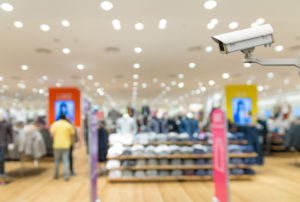 Picture of a security camera as part of a retail security system - blurry background showing the interior of a store.