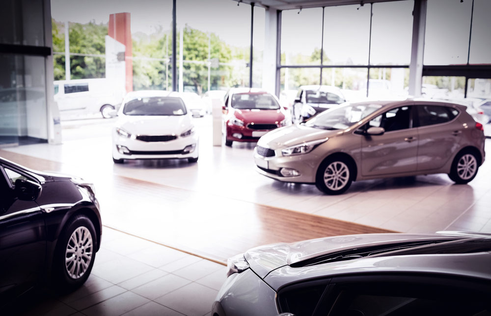 Interior of a car dealership with several cars in a showroom.