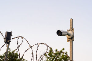 Picture of a part of a perimeter security system, showing a camera and fence topped with barbed wire.