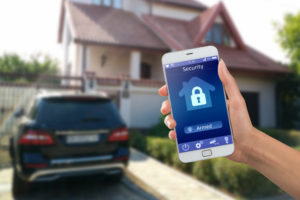 Smartphone with home security app in a hand, and an out-of-focus home in the background.