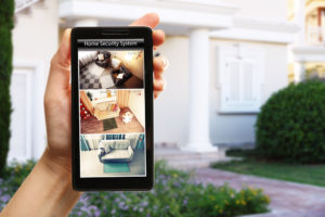 Close up of a hand holding a phone showing security camera feeds with blurred home in the background.