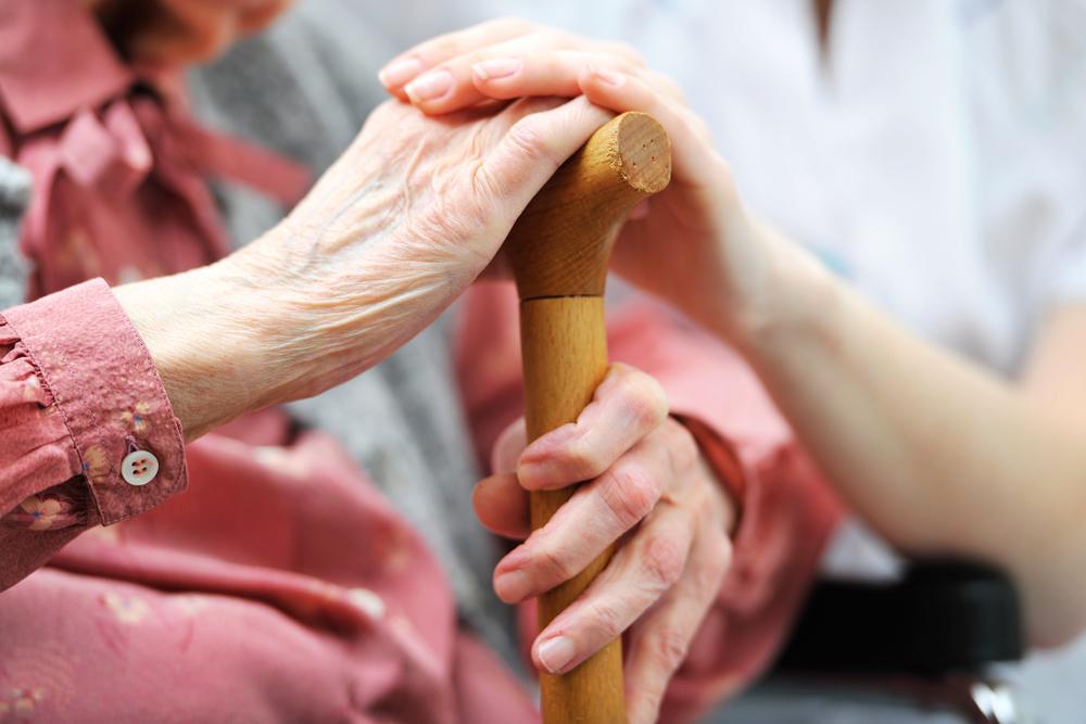 Close up of an elder woman's hands resting with her caregivers on her cane discussing personal emergency security system options.