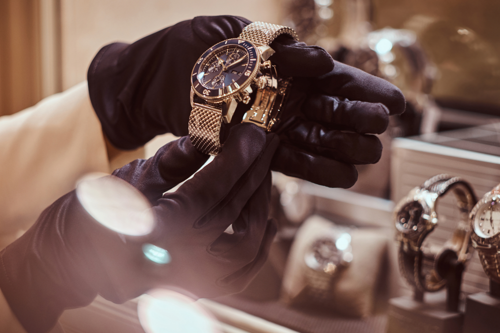 Close up of gloved hand stealing a watch from a retail store during a burglary.