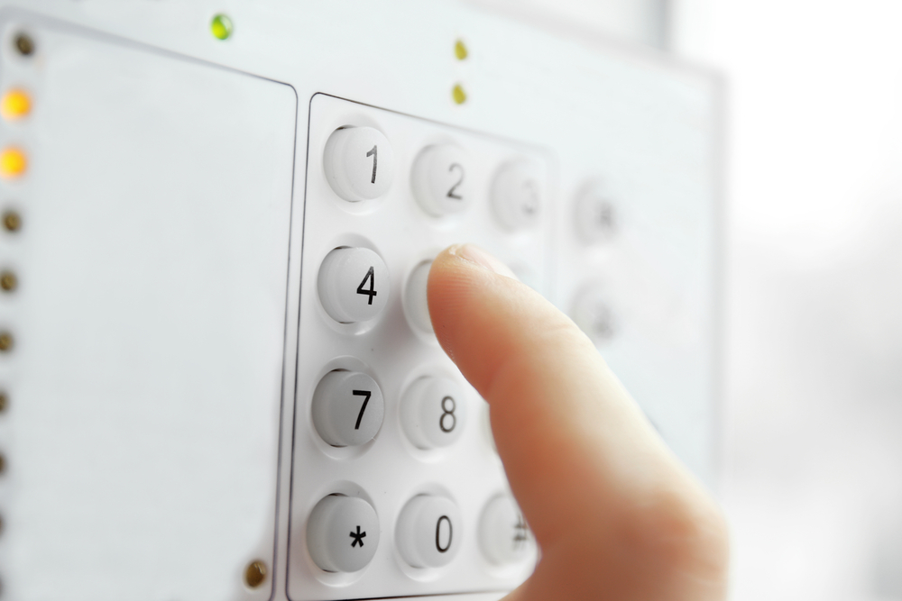 Close up of a finger entering a code on a security alarm system keypad.