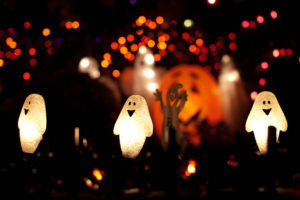 Close up of halloween decorations - ghosts and pumpkin lights - at night.