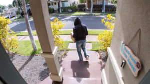Security camera picture of a thief walking away from a door with stolen packages.